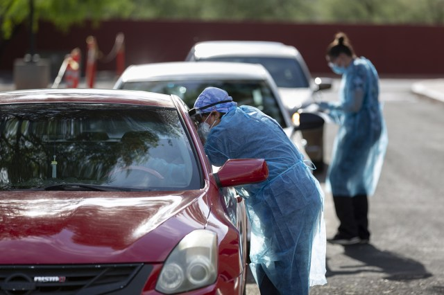 Healthcare workers wearing personal protective equipment (PPE) administer tests at a Covid-19 drive-thru testing site in Tucson, Arizona on July 13.