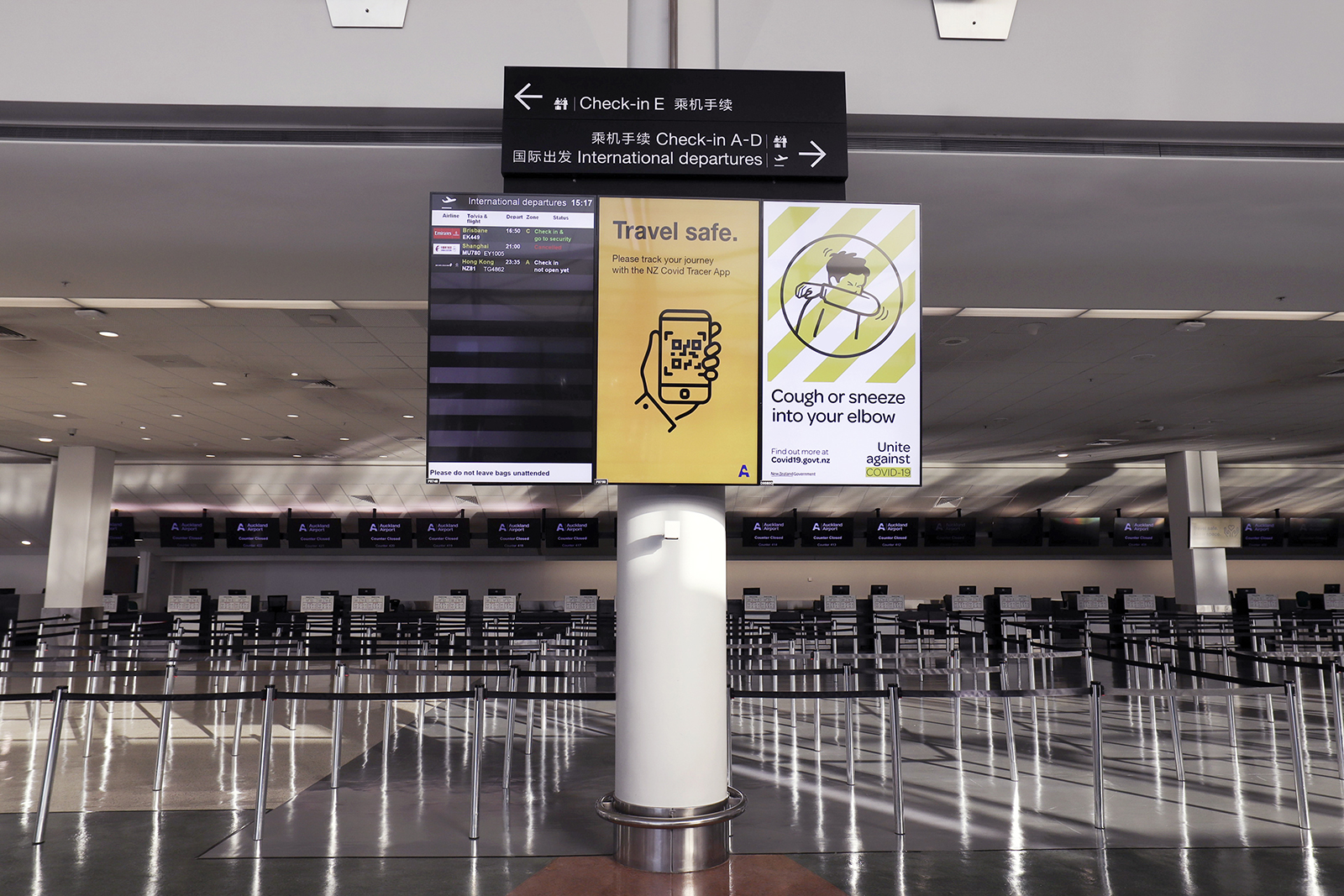 An information board displays a public health notice for the NZ Covid Tracer App in a deserted check-in hall at the International Terminal of Auckland Airport in Auckland, New Zealand, on Tuesday, July 7, 2020.