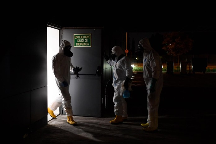 Members of the Spanish Military Emergencies Unit wearing protective gear prepare to disinfect the Lope de Vega Cultural Center in the Vallecas neighborhood where rapid tests for Covid-19 were conducted to residents of the area, on September 30 in Madrid.