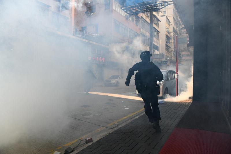 A Hong Kong police officer chases protesters through tear gas in Kowloon on Monday.