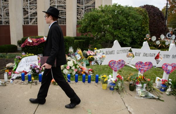 An orthodox jewish schoolboy passes a memorial for victims of the mass shooting that killed 11 people at the Tree Of Life Synagogue on Oct. 29, 2018 in Pittsburgh, Pennsylvania.