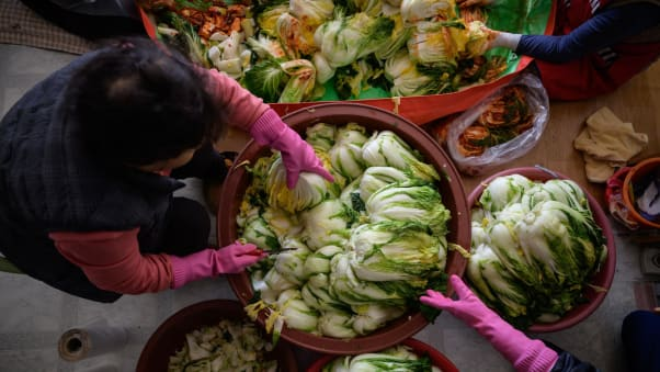 Women prepare cabbage to make kimchi during the traditional communal process known as 'kimjang.'