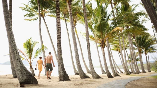A couple strolls through the palm trees on the beach in Palm Cove, a suburb of Cairns.