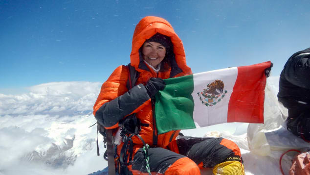 Viridiana Álvarez Chávez holds up a Mexican flag at the top of Mount Everest.