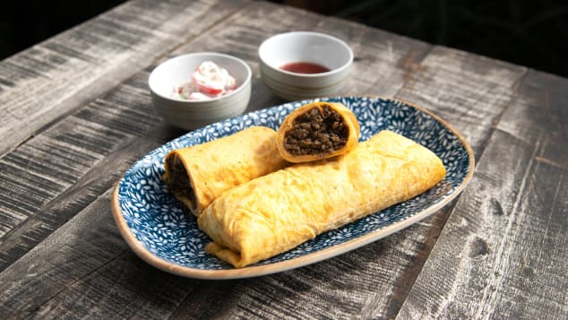Singaporean beef murtabak is an egg crepe wrapped around ground beef served with fresh lime, chili sauce and raita.