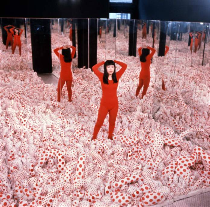 """Kusama pictured inside her work """"Infinity Mirror Room -- Phalli's Field"""" in 1965. The floor of the installation was covered with stuffed polka-dot phalluses."""