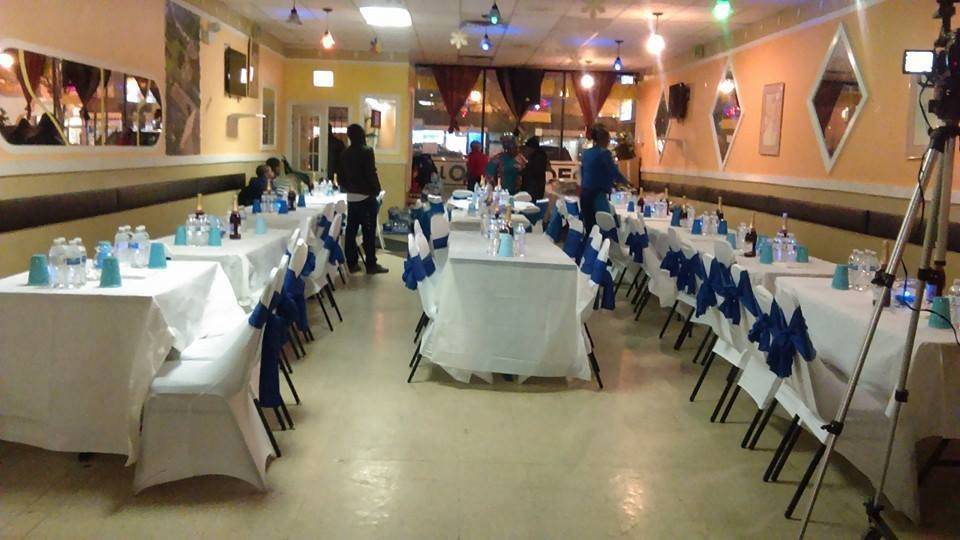 tables set for party with blue ribbons around backs of chairs