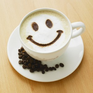 Cappuccino with smiley face and coffee beans.