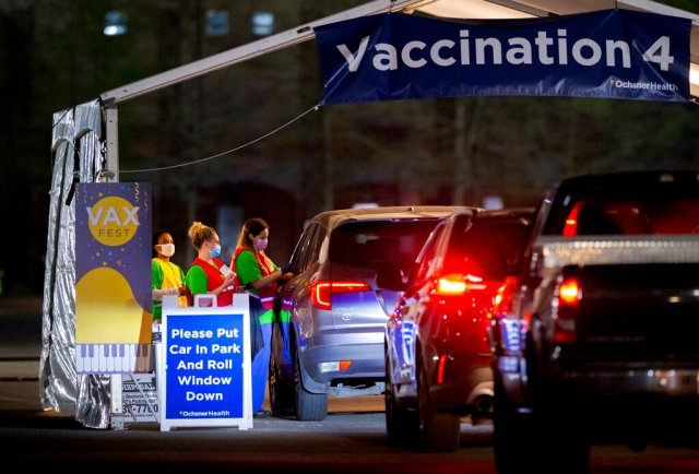 Ochsner nurses and volunteers give a Moderna COVID-19 vaccine at 5 a.m. during the 24-hour Max Fest at the Shrine on Airline Metairie near New Orleans Tuesday, March 30, 2021. Anyone who does not have an appointment can show up and get a vaccine until 7 a.m. this morning.  (David Grunfeld/The Advocate via AP)