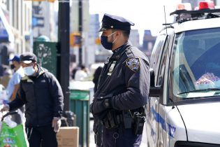 New York City Police Department Officer Rodney Hierro, right, keeps an eye on pedestrians and vendors along a busy section of Main Street in Flushing, a largely Asian American neighborhood, Tuesday, March 30, 2021, in the Queens borough of New York. Police have stepped up patrols in the neighborhood amid a rash of anti-Asian violence across the United States. (AP Photo/Kathy Willens)
