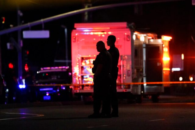 Two police officers stand outside an office building where a shooting occurred in Orange, Calif., Wednesday, March 31, 2021. The shooting killed several people, including a child, and injured another person before police shot the suspect, police said. (AP Photo/Jae C. Hong)