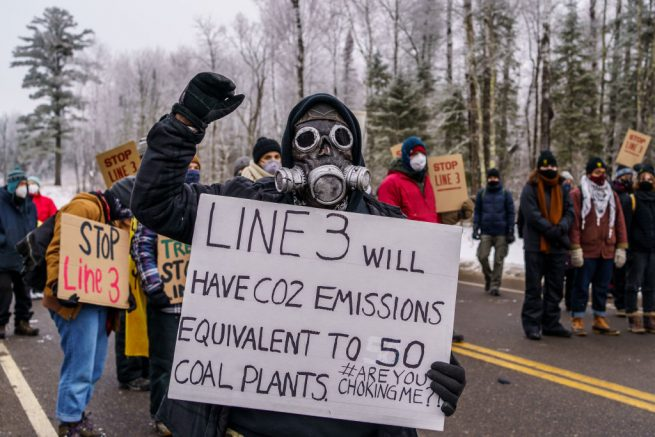 A Native American environmental activist holds a sign in front of the construction site for the Line 3 oil pipeline site near Palisade, Minnesota on January 9, 2021. - Line 3 is an oil sands pipeline which runs from Hardisty, Alberta, Canada to Superior, Wisconsin in the United States. In 2014, a new route for the Line 3 pipeline was proposed to allow an increased volume of oil to be transported daily. While that project has been approved in Canada, Wisconsin, and North Dakota, it has sparked continued resistance from climate justice groups and Native American communities in Minnesota. While many people are concerned about potential oil spills along Line 3, some Native American communities in Minnesota have opposed the project on the basis of treaty rights. (Photo by Kerem Yucel / AFP) (Photo by KEREM YUCEL/AFP via Getty Images)
