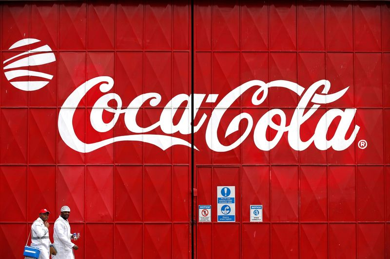 Workers walk past a Coca Cola logo painted on a gate at a Coca Cola factory in Nairobi