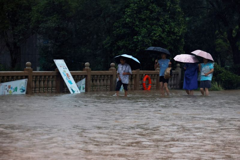 People holding umbrellas amid heavy rainfall wade through floodwaters on a bridge in Hebi