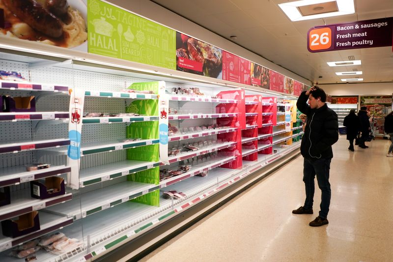 FILE PHOTO: A man stands next to shelves empty of fresh meat in a supermarket, as the number of worldwide coronavirus cases continues to grow,  in London