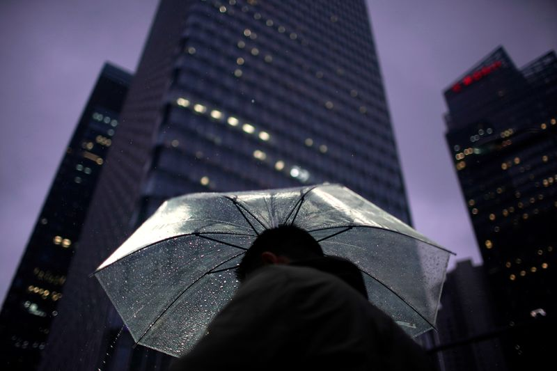 A man walks with an umbrella in Lujiazui financial district in Pudong