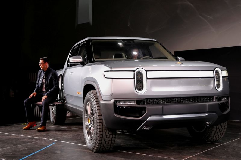 FILE PHOTO: Rivian's CEO, Scaringe, with the R1T all-electric pickup truck at LA Auto Show in Los Angeles