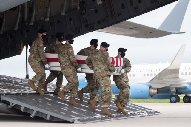 A transfer case with the remains of Army Staff Sgt. Ryan C. Knauss, 23, of Corryton, Tennessee, are carried off of a military aircraft as US President Joe Biden attends the dignified transfer at Dover Air Force Base in Dover, Delaware, August, 29, 2021, one of the 13 members of the US military killed in Afghanistan last week. - President Joe Biden prepared Sunday at a US military base to receive the remains of the 13 American service members killed in an attack in Kabul, a solemn ritual that comes amid fierce criticism of his handling of the Afghanistan crisis. Biden and his wife, Jill, both wearing black and with black face masks, first met far from the cameras with relatives of the dead in a special family center at Dover Air Force Base in Delaware.The base, on the US East Coast about two hours from Washington, is synonymous with the painful return of service members who have fallen in combat. (Photo by SAUL LOEB / AFP) (Photo by SAUL LOEB/AFP via Getty Images)