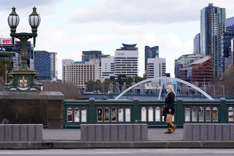 FILE PHOTO: A lone woman, wearing a protective face mask, walks across a city centre bridge a in Melbourne