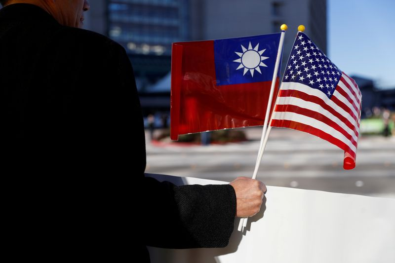 FILE PHOTO: A demonstrator holds flags of Taiwan and the United States in support of Taiwanese President Tsai Ing-wen during an stop-over after her visit to Latin America in Burlingame