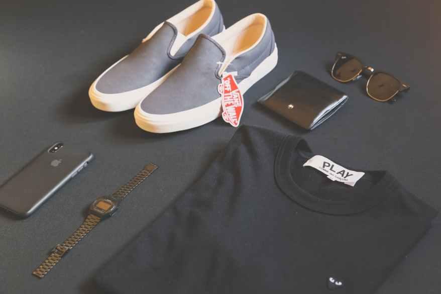 pair of gray vans low top sneakers beside black shirt sunglasses and watch