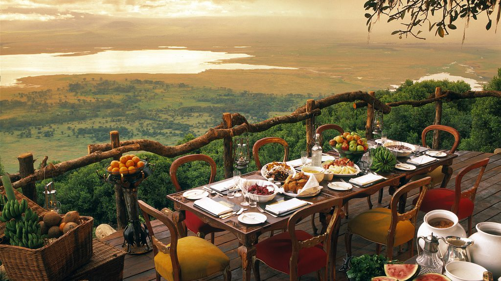 a banquet table overlooking mountains at the Ngorongoro Crater Lodge in Tanzania