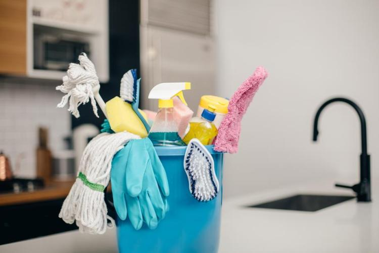 a bucket of cleaning supplies on a kitchen counter