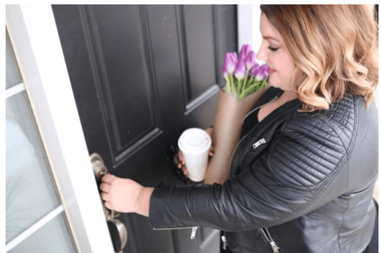 a woman opening the front door to her home