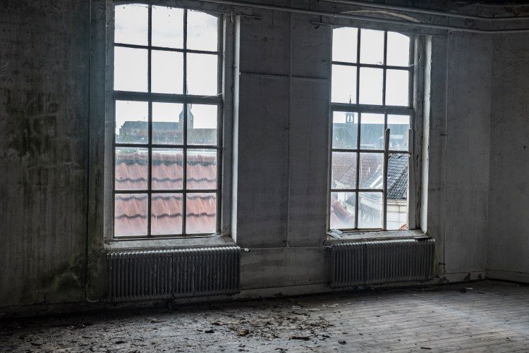 Abandoned building interior with damaged floors and ceilings. Light is coming in through the dirty and damaged windows.