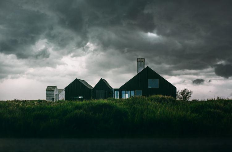 a dark home in a field under black clouds