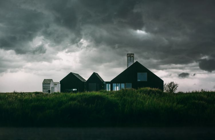 a dark home in a field under black clouds