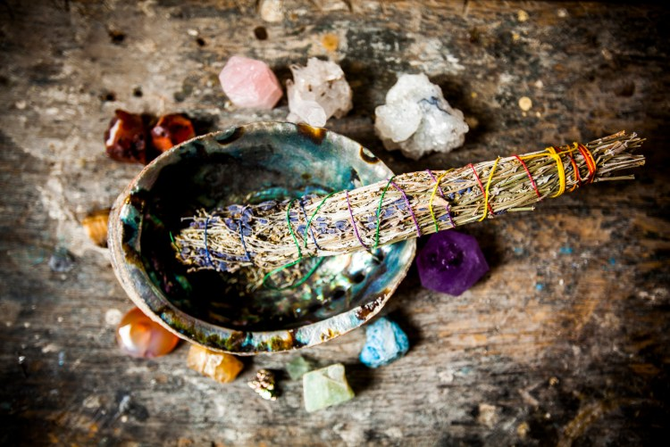 Lavendar and Sage bundle Burning, in a bowl surrounded by crystals