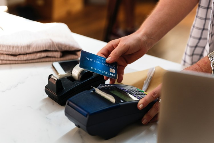 a person charging a credit card with a POS machine