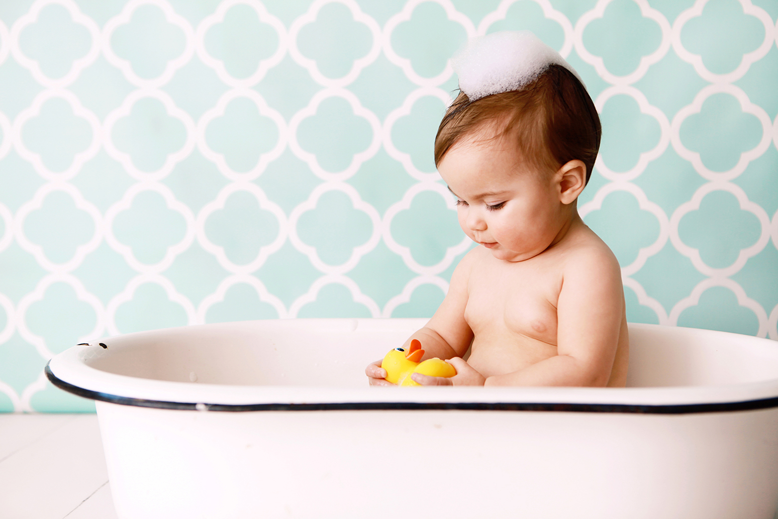 a baby in a small tub with a patterned wallpaper background