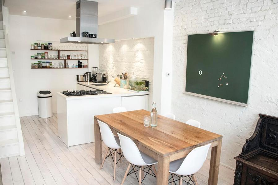 a kitchen and dining room with white furnishings