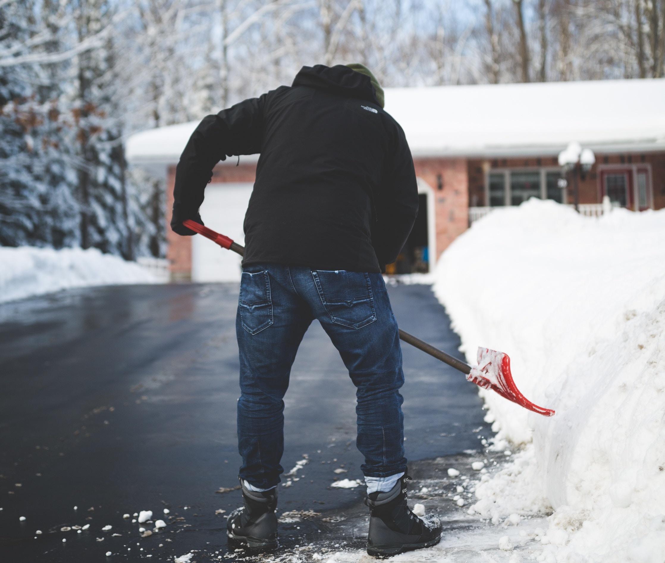 a man shovelling snow off a driveway