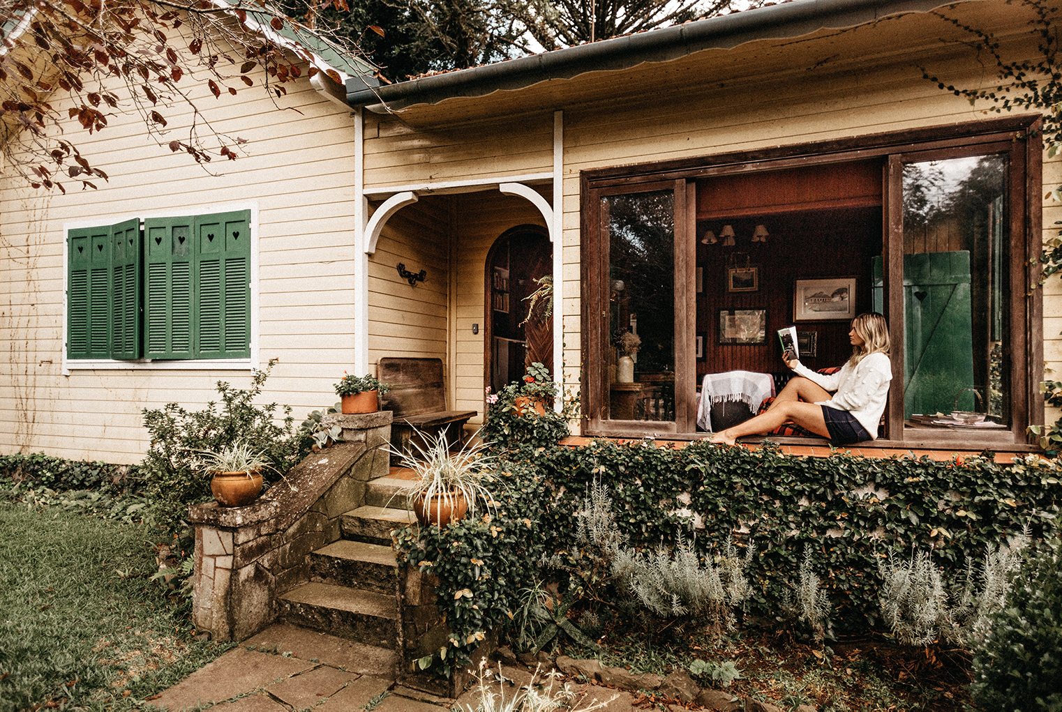 a woman reading a book on the front porch of a house