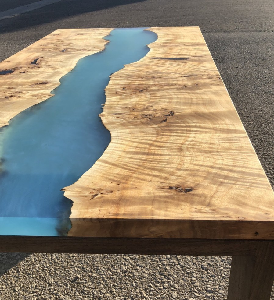 a live edge table with a blue resin middle