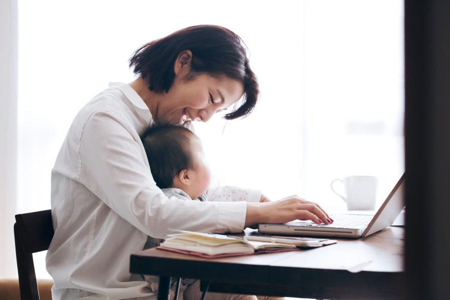 a woman with her baby on her lap while working on a laptop