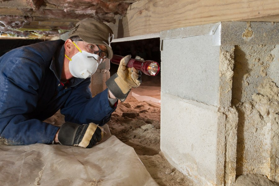 a man inspecting the foundation of a home within the crawl space