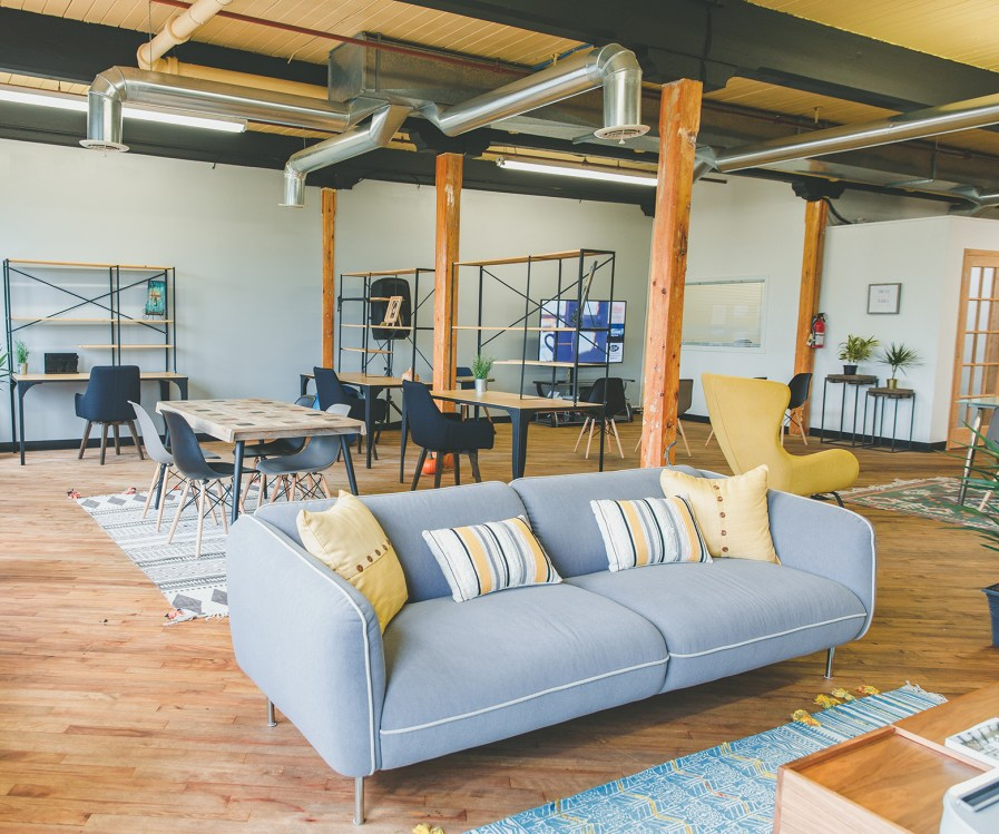 An open-concept loft space with exposed beams, pipes in the ceiling and wooden support beams