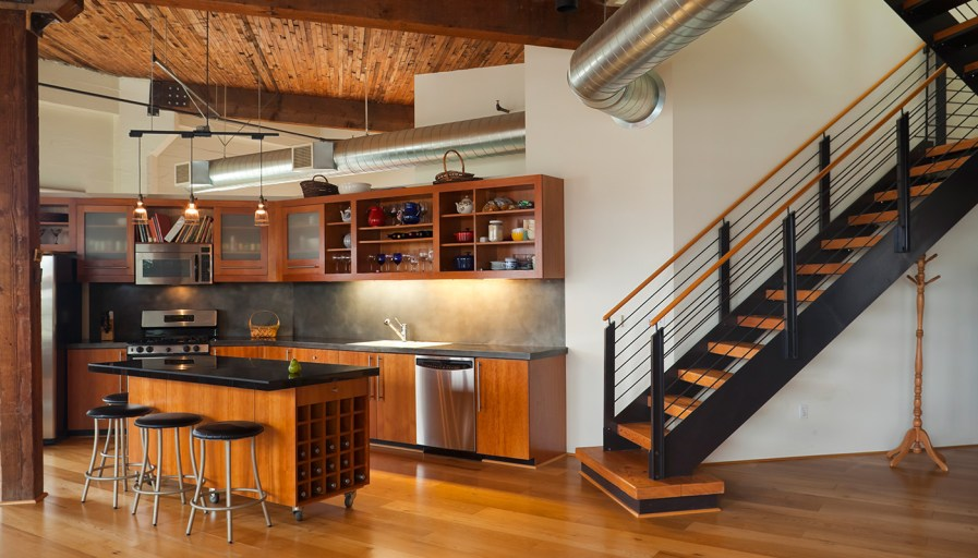 Wood and black iron staircase descending to a kitchen.