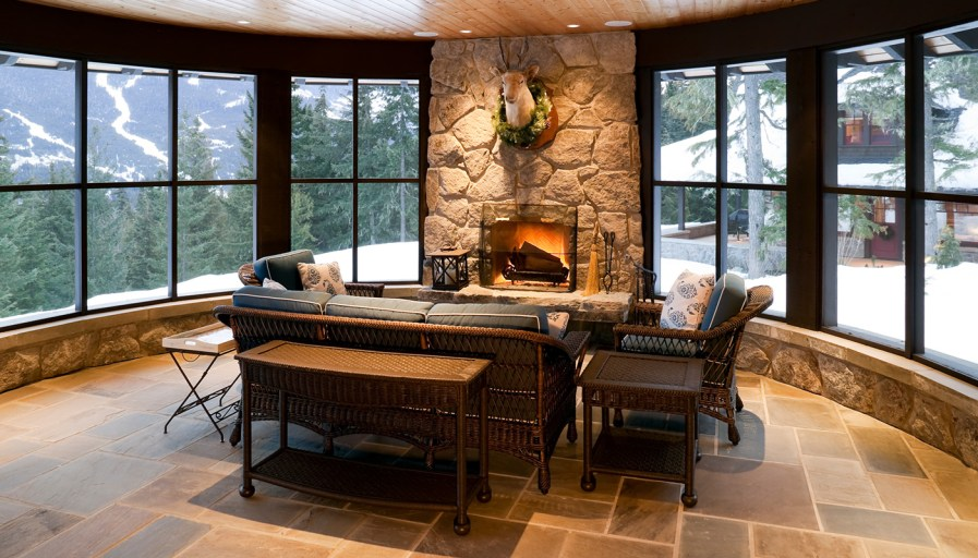 Stone fireplace surrounded by floor to ceiling windows on either side.
