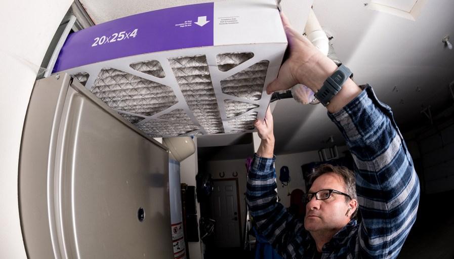 Man replacing furnace filter.