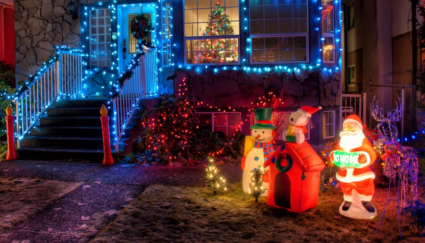 House decorated with blue and red holiday lights and blow up snowman