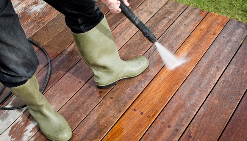 Person spraying their deck.