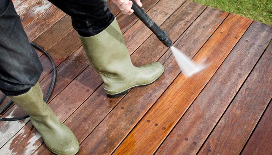 Person spraying their deck.