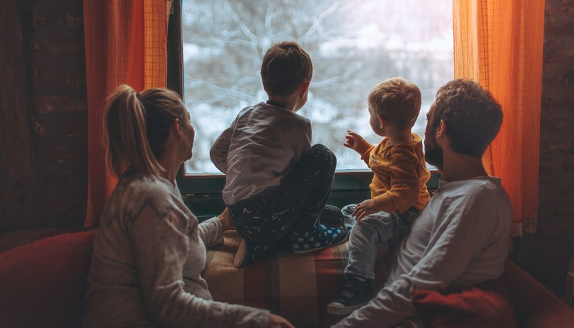 Family sitting by window looking out at snow covered trees.