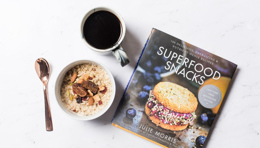 Cookbook beside oatmeal and cup of coffee