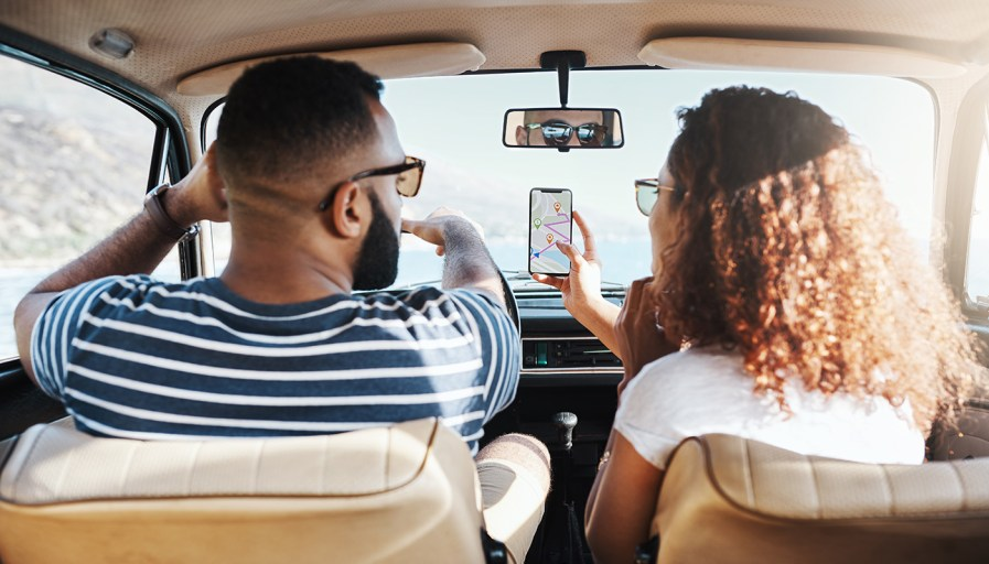 Two people looking at a map on their phone while driving